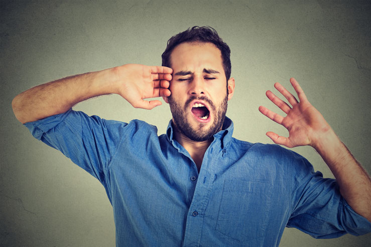 Man yawning and stretching out arms from lack of sleep