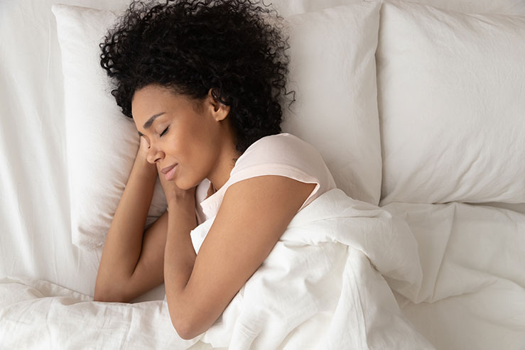 Woman sleeping peacefully in bed after following some sleep tips